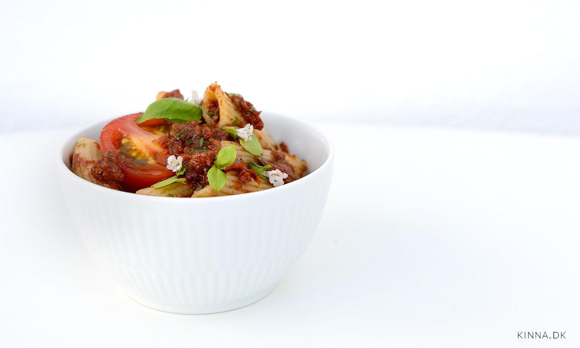 Kold pastasalat vendt i dressing med soltørrede tomater, balsamico, hvidløg og basilikum